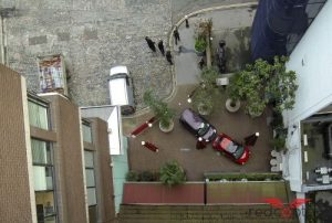 Image showing a courtyard with parked cars and trees