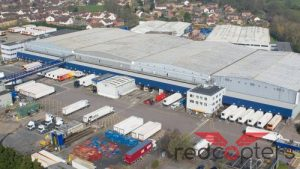 Image shows a large industrial building with lorries being loaded in the foreground