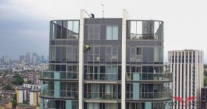 Image shows a man abseiling down apartment building